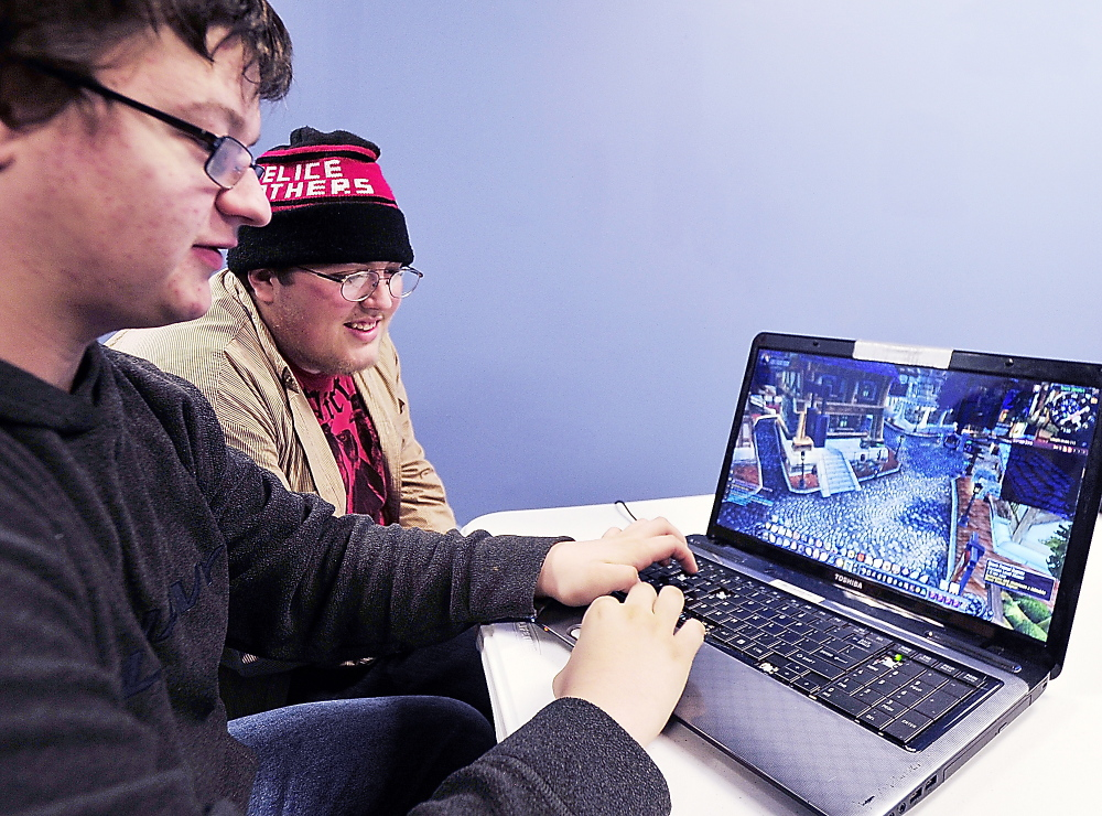 "Victor Smith of Portland, left, plays his customized character with dozens of others online Thursday in ""World of Warcraft."" Helping Smith with strategyis his friend, Keegan Beal."