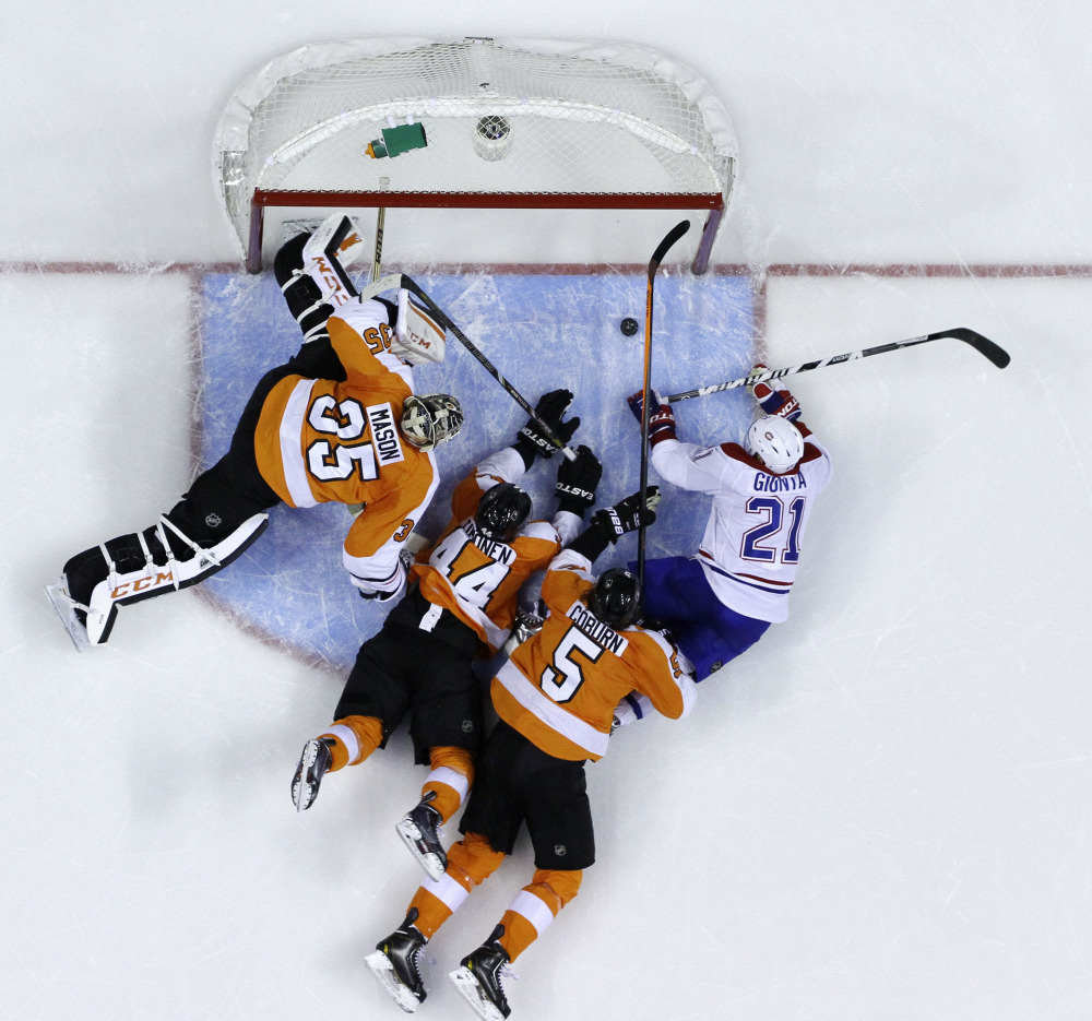 Brian Gionta, right, of the Montreal Canadiens knocks in a goal with his hand while surrounded by Philadelphia's Braydon Coburn, Kimmo Timonen and Steve Mason during a 2-1 win by the Flyers on Thursday. The score was subsequently overturned by the officials.