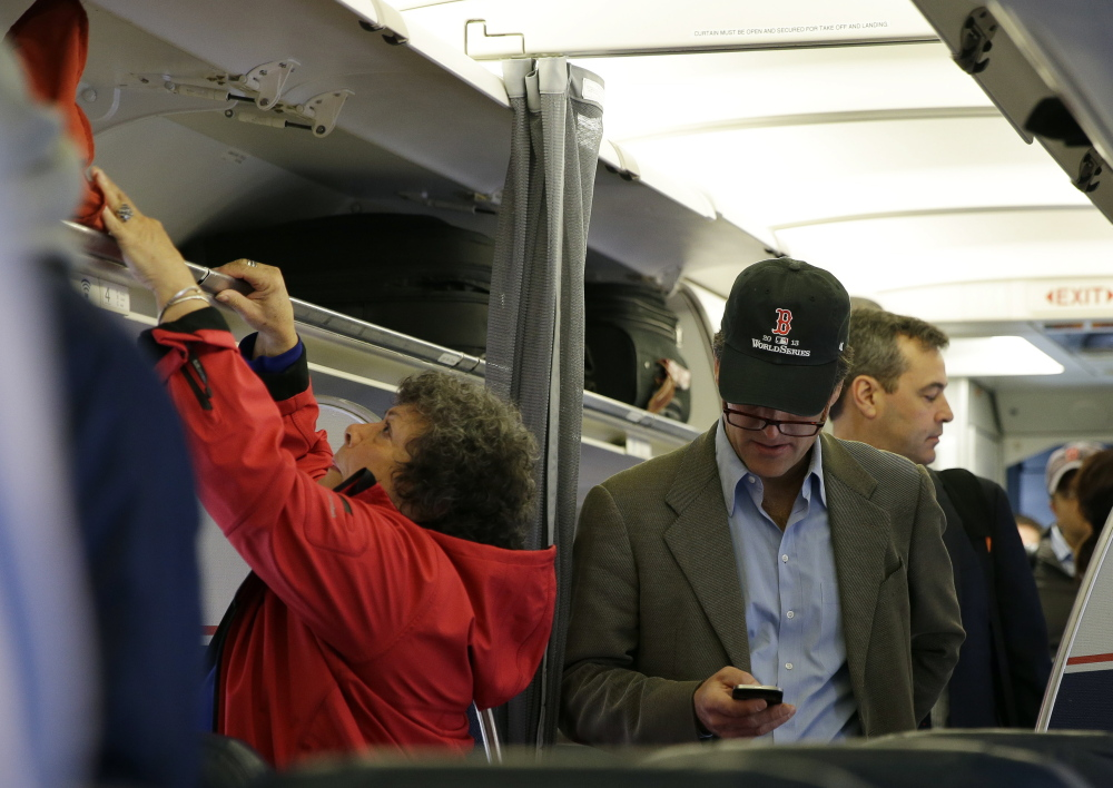 A passenger checks his cellphone while boarding a flight in Boston. For the past decade, fliers haven't been able to use electronic devices while planes are below 10,000 feet because they might interfere with cockpit instruments, but the Federal Aviation Administration has decided that interference isn't a concern anymore.
