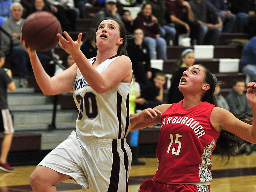 Sadie Nelson of Windham goes in for a fast-break basket as Emma Hall of Scarborough defends during their SMAA game Friday night in Windham. Nelson scored 20 points to lead the Eagles to a 48-43 win.