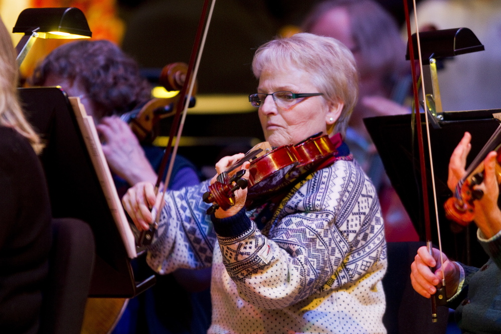 "Carl D. Walsh/Staff Photographer Portland Symphony Orchestra violist Ann Stepp plays during the final ""Magic of Christmas"" at Merrill Auditorium in Portland on Thursday. Her daughter surprised her before the rehearsal by telling her she was also performing in the show."