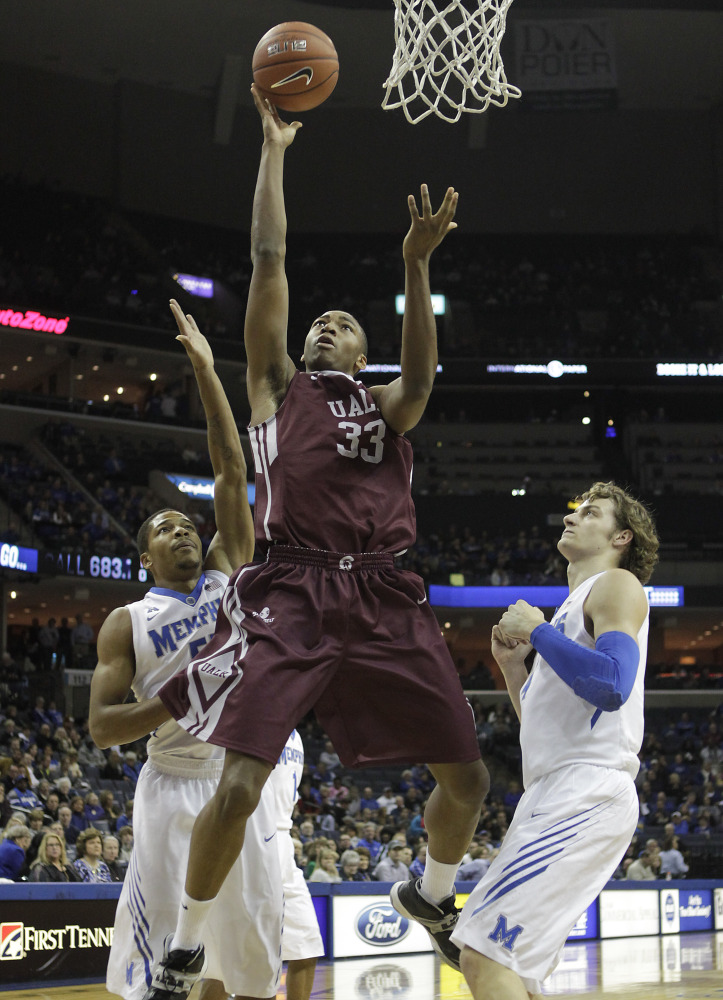 Arkansas-Little Rock forward James White goes to the basket between Memphis guard Geron Johnson, left, and forward Austin Nichols during Friday's game in Memphis.
