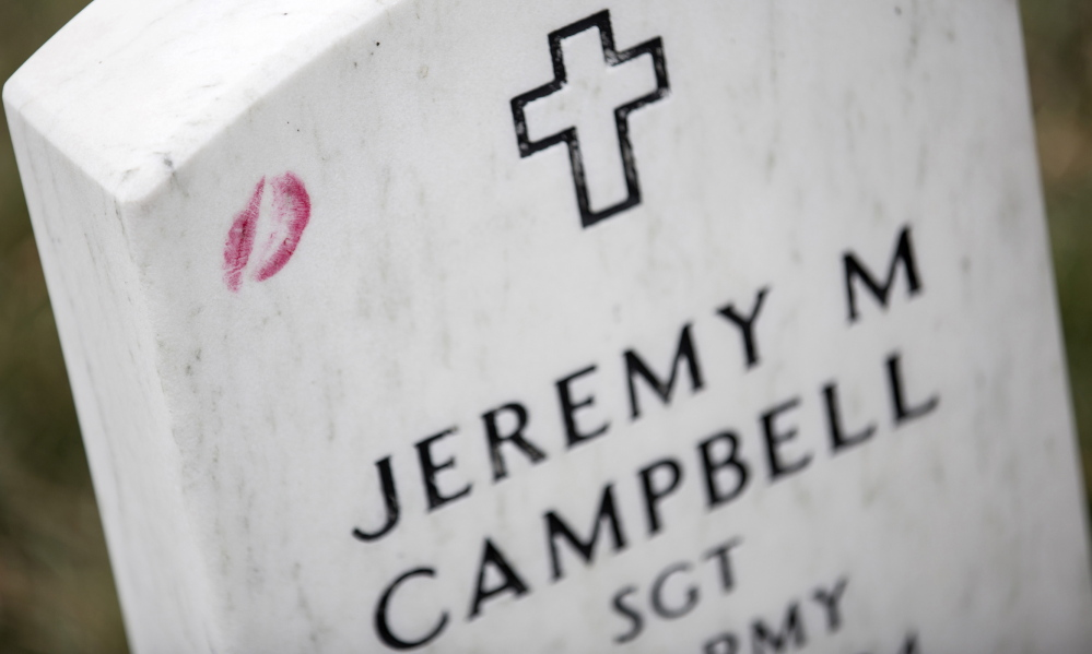 A lipstick kiss rests on the gravestone of Jeremy M. Campbell in Section 60 at Arlington National Cemetery, the site of an annual Wreaths Across America event founded in Maine.