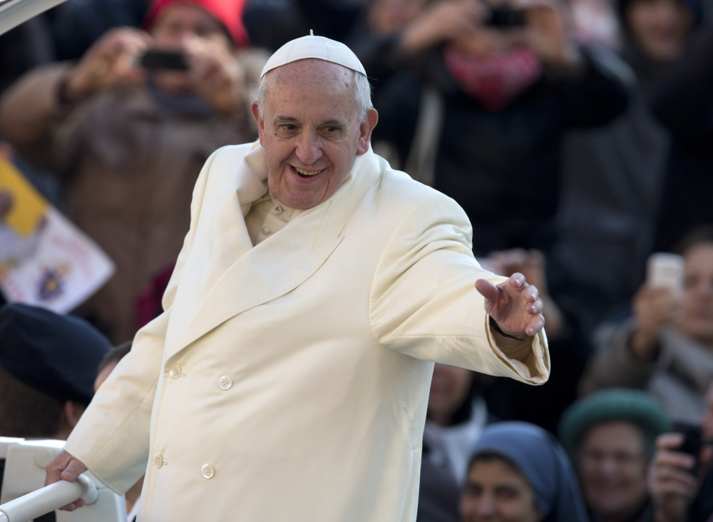 Pope Francis waves as he arrives for his weekly general audience in St. Peter's Square at the Vatican, Wednesday.