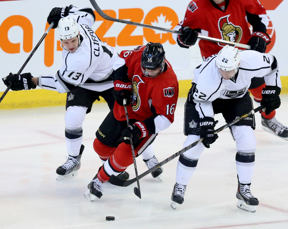 Ottawa's Clarke MacArthur is checked by Los Angles Kings Kyle Clifford, left, and Trevor Lewis during the first period of Saturday's game in the Canadian capital.