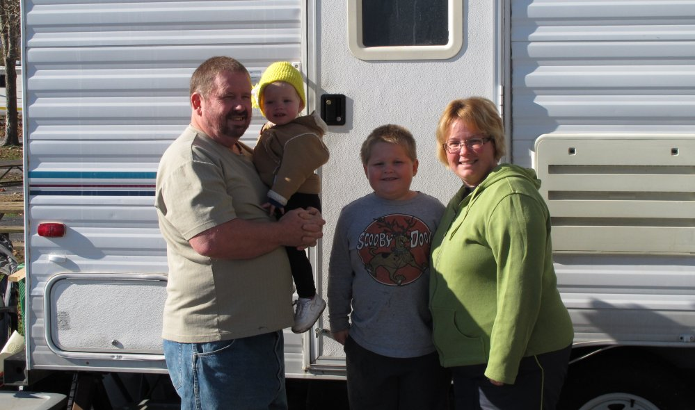 Ron and Kristin Dale and their children stand outside their 24-foot-long camper at a campground Thursday outside Campbellsville, Ky. The family is among many RV owners who converge on area campgrounds to take seasonal jobs at Amazon.com.