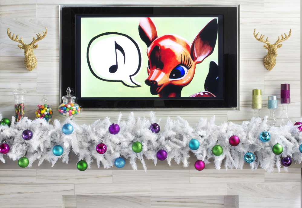Bold colors and whimsical decorating touches around a mantel, including images copied onto a DVD and shown on a TV screen, emphasize the playful side of holiday celebrations.