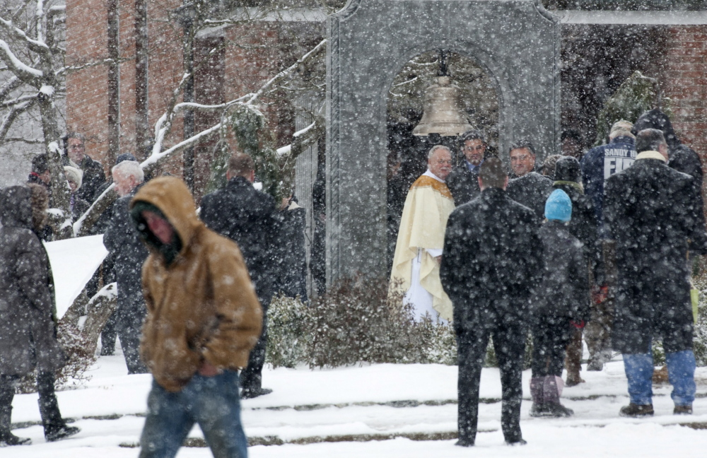 People gather following Mass at St. Rose church as a permanent memorial is dedicated to the victims of the Sandy Hook Elementary School shooting in Newtown, Conn.