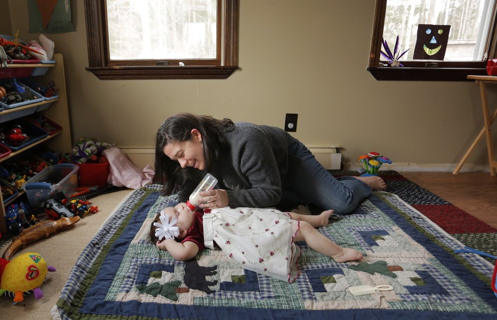 Meagan Patrick plays with her daughter, Addelyn, at their Acton home earlier this month. The 13-month-old has severe epilepsy, and her mother is taking steps to become a resident of Colorado, where the family wants to try treating the child with a strain of medical marijuana that's produced there but can't legally be brought back to Maine.