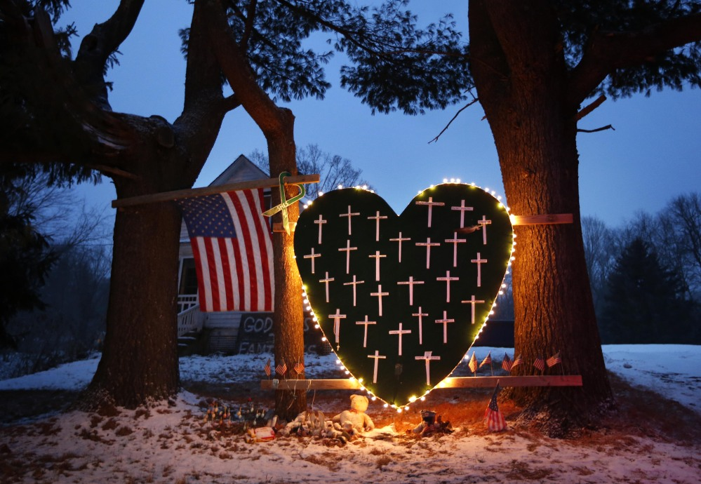 A makeshift memorial with crosses for the victims of the Sandy Hook massacre stands outside a home in Newtown, Conn., Saturday, Dec. 14, 2013, the one-year anniversary of the shootings.