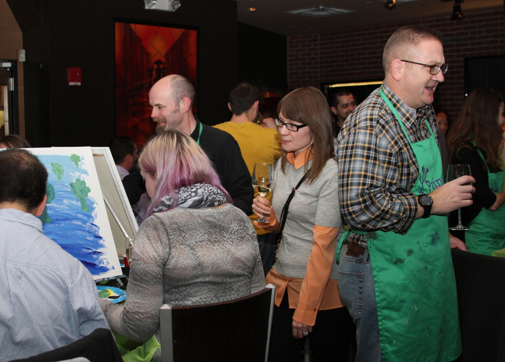 Employees from software company Lattice Engines' Boston office participate in a Paint Nite class earlier this month. Paint Nite gives painting lessons at bars and restaurants. About 65 people attended, painting trees while they drank and ate hors d'oeuvres.
