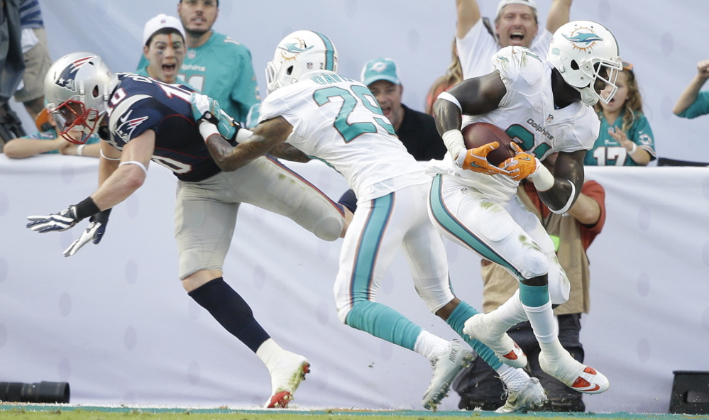Miami's Michael Thomas intercepts a Tom Brady pass intended for New England receiver Austin Collie, who's double-teamed by Will Davis, on the last play of Sunday's game in Miami Gardens. Despite the loss, the Patriots still are in control of the AFC East and could wrap up the title with a win in the next two weeks.