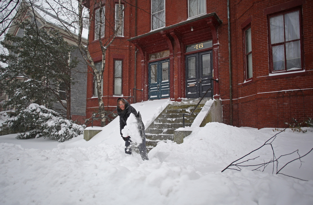 Andrea Zimble shovels her front steps and sidewalk on Deering Street in Portland on Sunday after an overnight storm dropped a foot of snow on the city. (Amelia Kunhardt/staff photographer)