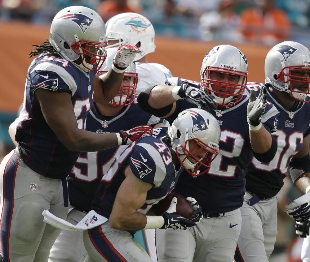 New England Patriots defensive back Nate Ebner (43), center, is congratulated by his teammates, Dont'a Hightower (54) and defensive end Jake Bequette (92), after Ebner recovered a fumbled field goal by the Miami Dolphins during the first half of Sunday's game.