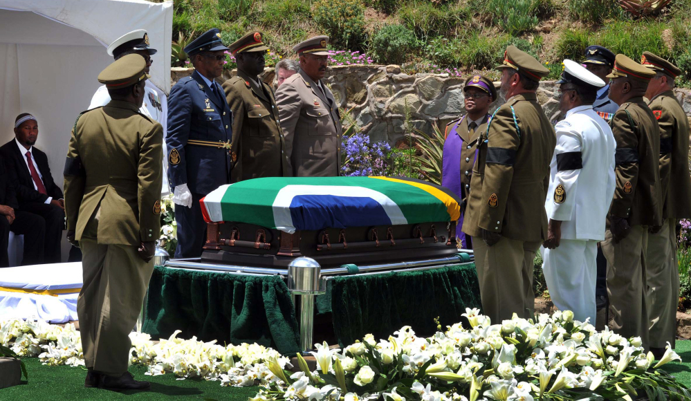 Military soldiers stand at attention over South African President Nelson Madela's casket before his burial in his home village of Qunu, South Africa, Sunday, Dec. 15, 2013.