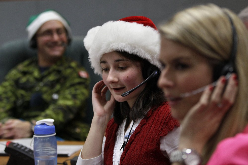 Volunteer Katherine Beaupre takes phone calls from children on Christmas Eve 2012 asking where Santa is and when he will deliver presents to their house,during the annual NORAD Tracks Santa Operation, at the North American Aerospace Defense Command, or NORAD, at Peterson Air Force Base, in Colorado Springs, Colo.