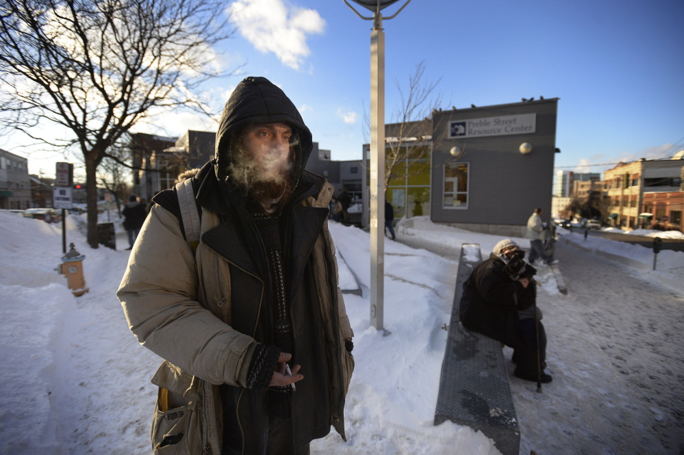 Matt Coffey, who is homeless, stays bundled up in Monday's cold as he smokes outside the Preble Street Resource Center in Portland. Coffey says he usually sleeps outside at night even when it's bitter cold, staying warm enough using his survival skills.