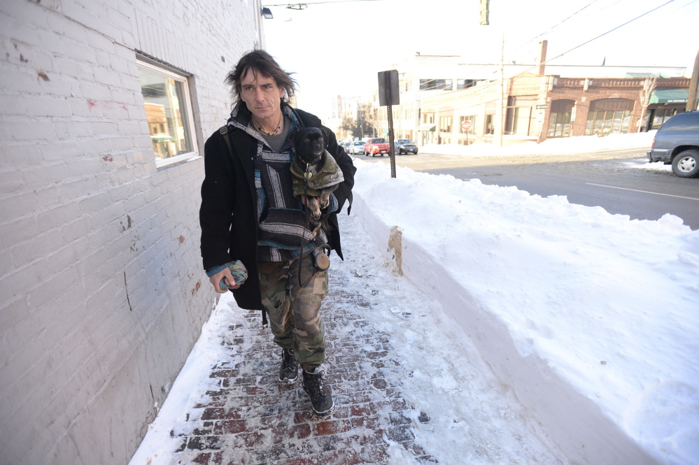 """Robin Bartlett, who is homeless, carries his dog, Bella, as he heads to the Preble Street Resource Center in Portland. Staying warm is """"all about the layers. I'm wearing like three pairs of long johns right now,"""" he said."""
