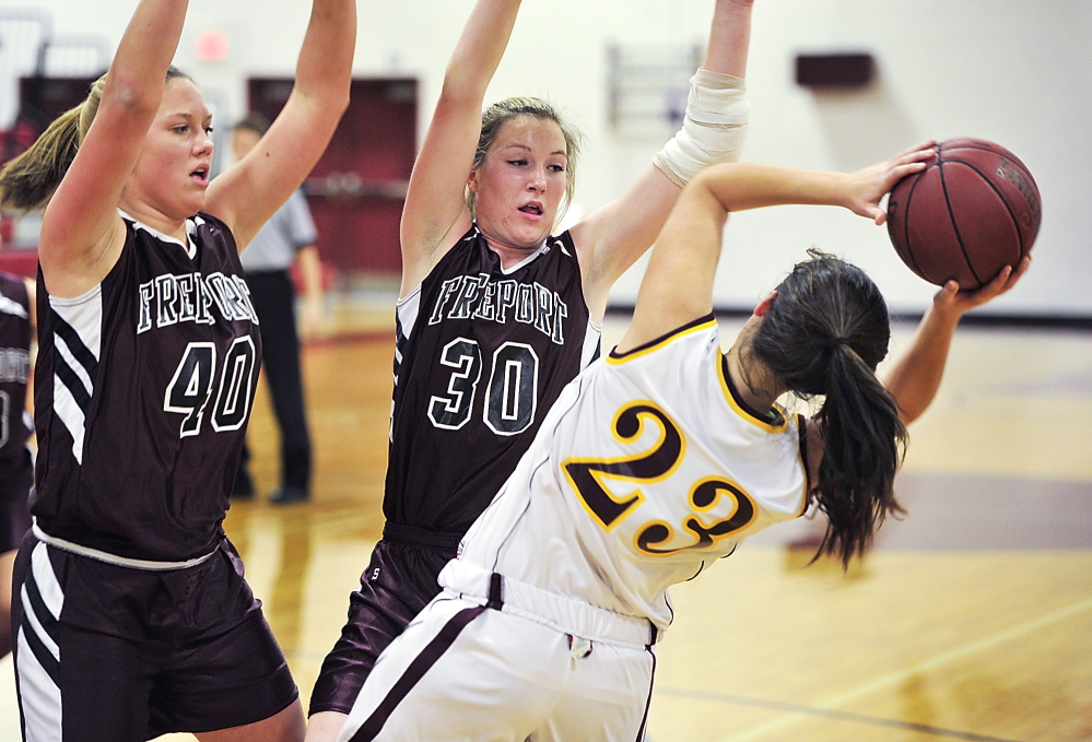 Emma O'Rourke of Cape Elizabeth gets trapped in the corner by Freeport's Jessica Wall, left, and Nina Davenport. O'Rourke made 5 of 6 free throws in the fourth quarter to help the Capers secure their victory.