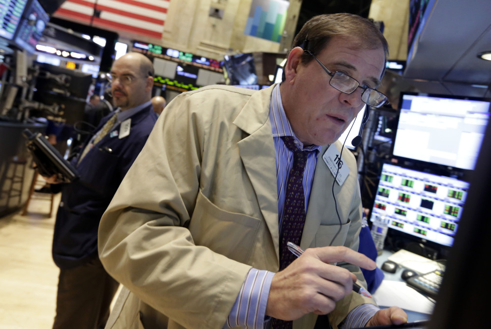 Trader Jonathan Niles, right, works on the floor of the New York Stock Exchange Monday. U.S. stocks rose sharply on Monday, powered by two big corporate deals and news that suggests the economy is getting stronger.