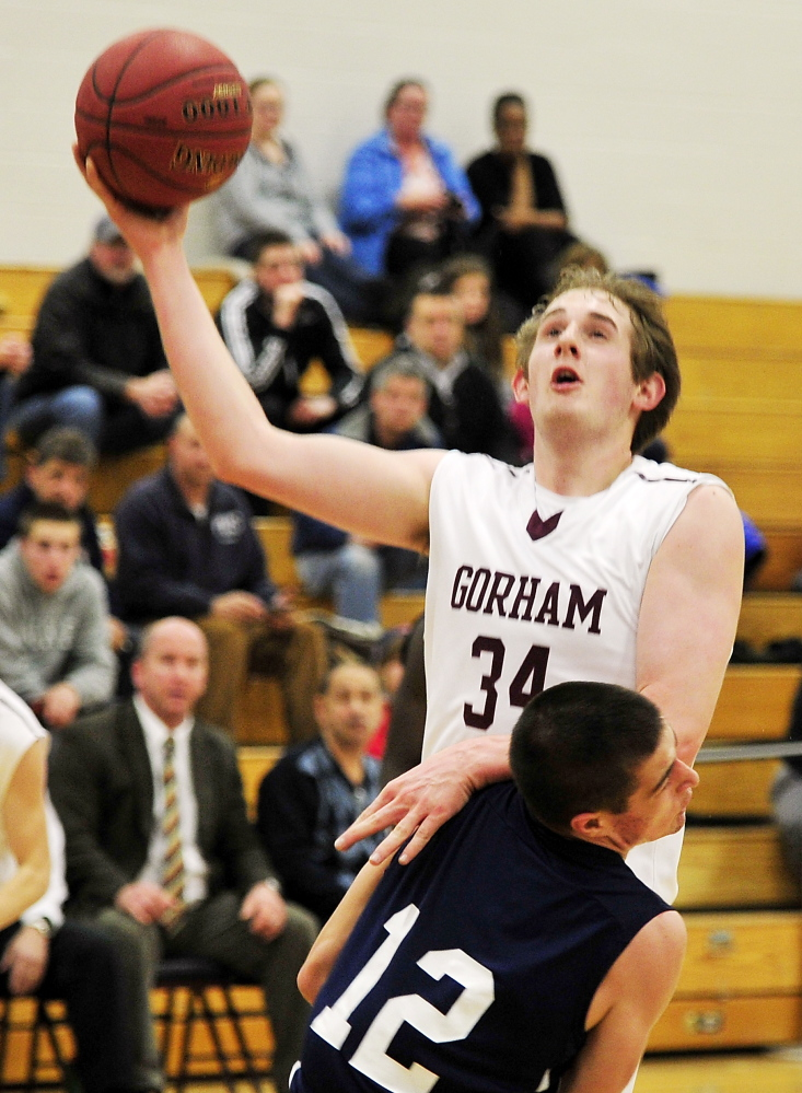 Gorham's Sam Kilborn lays it up over Portland's Justin Zukowski in Gorham Tuesday.