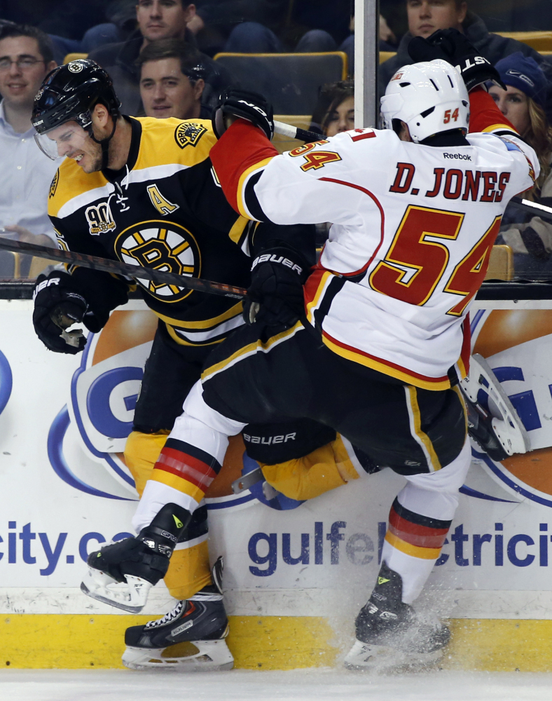 Boston Bruins center David Krejci collides with Calgary Flames right wing David Jones along the boards in Boston Tuesday night.