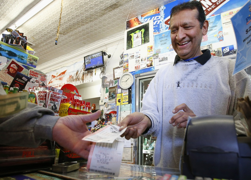 Keith Ganatra, owner of the Del Monte Market in Laveen, Ariz., sells Mega Millions lottery tickets on Tuesday. With tickets selling well, the jackpot for tonight's drawing is now at an estimated $636 million – the second-biggest lottery prize in U.S. history.