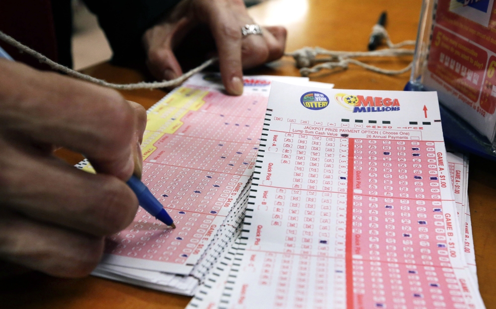 A woman picks her Mega Millions lottery numbers at a shop in New York's Penn Station Tuesday. Mega Millions changed its rules in October to help increase the jackpots by lowering the odds of winning the top prize.