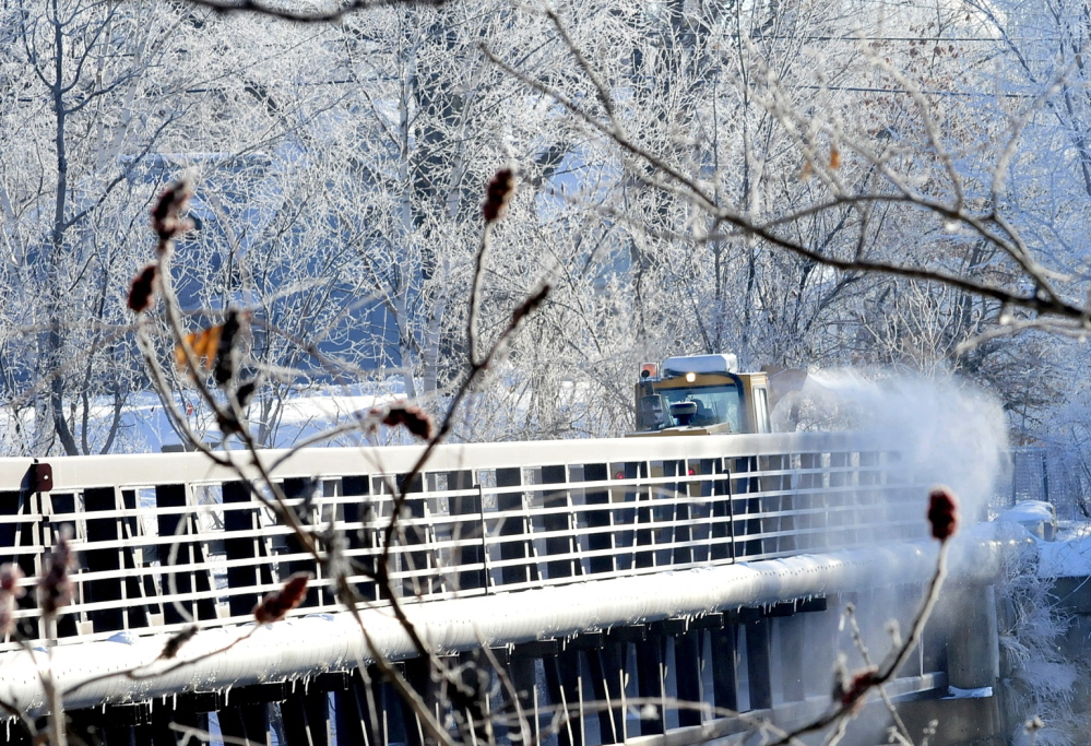 A Skowhegan Highway Department snowblower clears snow from the ice-covered walking bridge Tuesday. Freezing spray from the Kennebec River covered nearby tree limbs with ice.