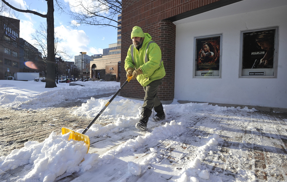 Ron Langway of Portland cleans snow from the sidewalks around the Nickelodeon movie theater Monday. Langway works for the management company that owns the building. More snow is expected Tuesday.