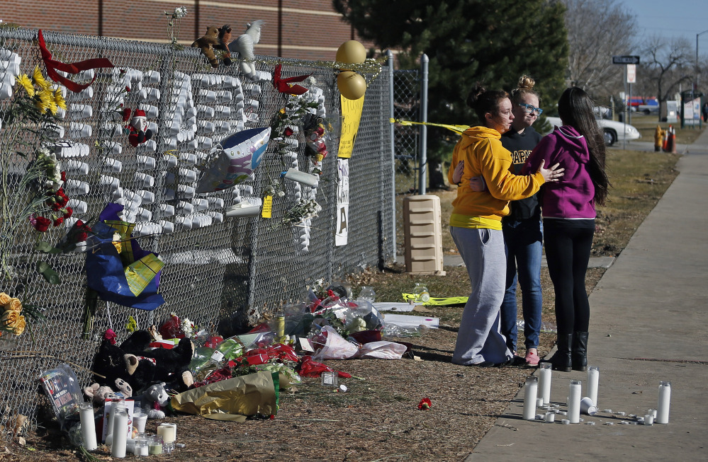 Arapahoe High School students hug after leaving items at a makeshift tribute site three days after a shooting attack at the school in Centennial, Colo., Monday, Dec. 16, 2013. They are, left to right, Hannah Eddy, Gavyn Bills, and Vania Arevalo. During the attack, the shooter shot a classmate in the head at close range with a shotgun, before killing himself.