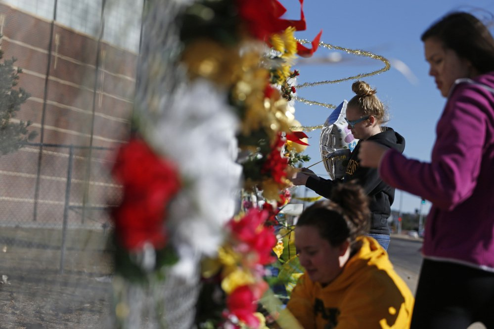 Arapahoe students leave flowers and other items at a makeshift tribute site three days after a shooting attack at Arapahoe High School in Centennial, Colo., Monday, Dec. 16, 2013. They are from left, Hannah Eddy, at bottom, Gavyn Bills, and Vania Arevalo. During the attack, the shooter shot a classmate in the head at close range with a shotgun, before killing himself.
