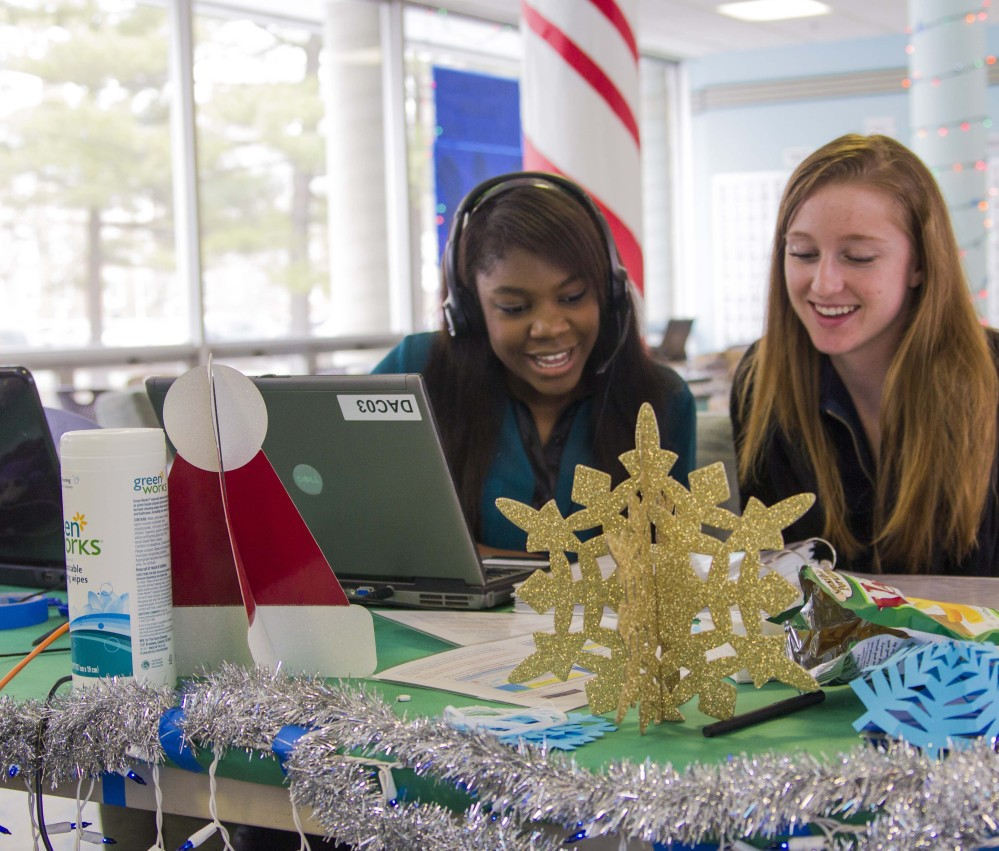 University of Illinois students Pauline Chitamdo, left, and Patti Grzyb sing to callers as part of the hall's annual Dial-A-Carol program in Champaign, Ill.