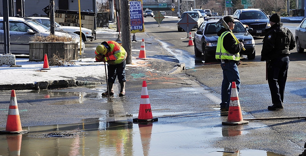Central Maine Power and Portland Water District workers deal with a water main break in June. The district wants to raise rates to pay for replacement of aging pipes.