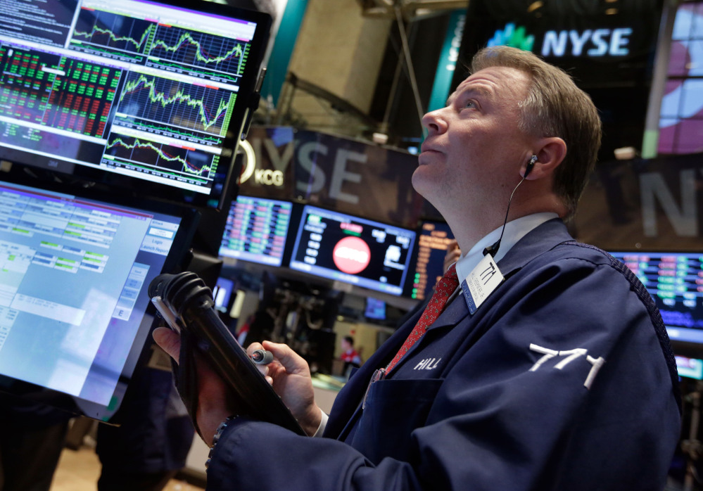 Trader F. Hill Creekmore works on the floor of the New York Stock Exchange on Wednesday. Stocks surged after the Federal Reserve decided the U.S. economy was strong enough for it to reduce its stimulus efforts.