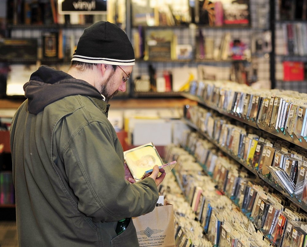 "Brady Alden of Gray shops for CDs at Bull Moose in Portland. He likes to wander into local stores, he said, because ""I think you find better stuff – things you weren't even looking for that catch your eye."""
