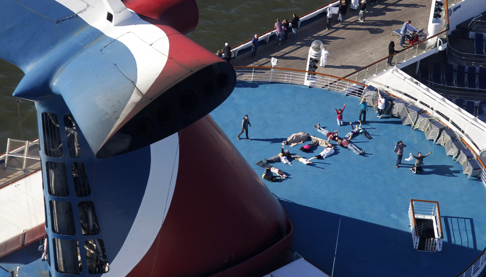 """Passengers spell out the word """"HELP"""" aboard the disabled Carnival Lines cruise ship Triumph as it is towed to harbor off Mobile Bay, Ala., in this Feb. 14, 2013, photo."""