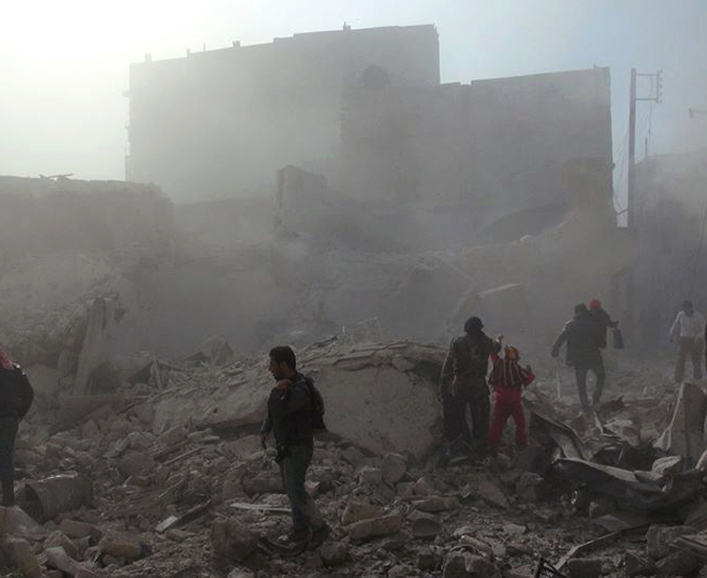 People inspect the rubble Tuesday following four days of Syrian government airstrikes in Aleppo, Syria. In a relentless offensive, helicopters dumped bombs packed with explosives and fuel on rebel-held neighborhoods.