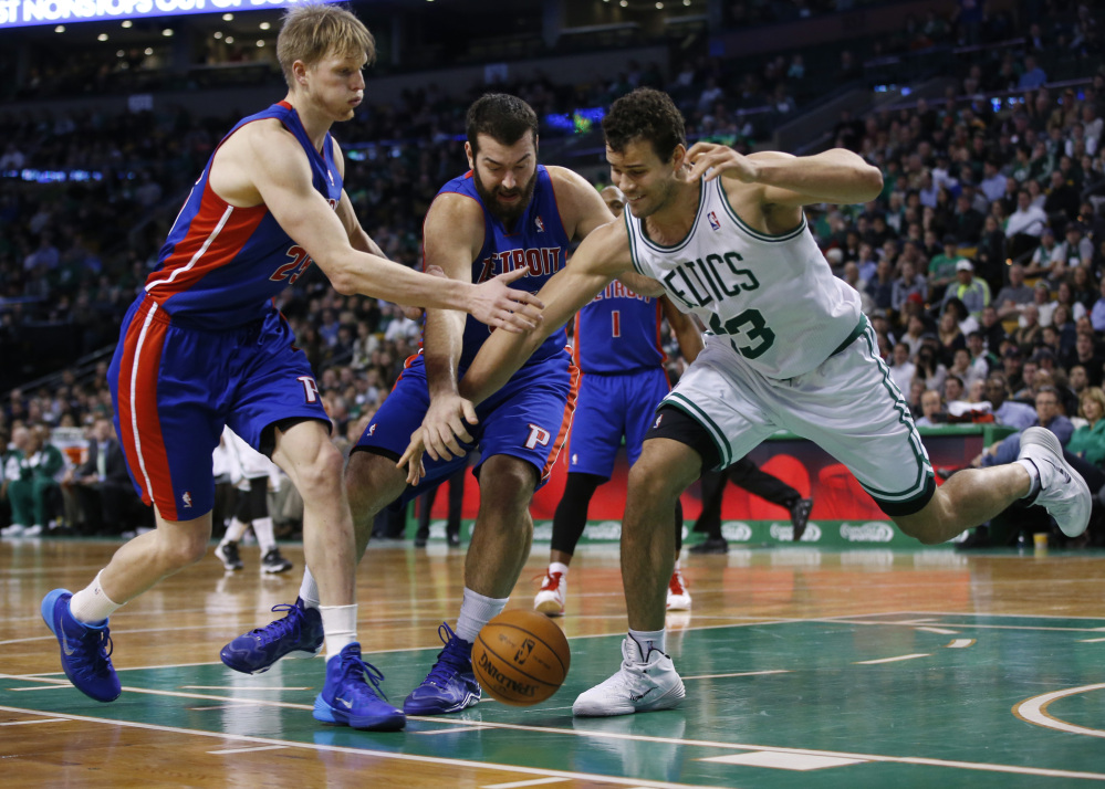 Celtics power forward Kris Humphries, right, goes for a loose ball against Pistons forwards Kyle Singler, left, and Josh Harrellson during the second half of Detroit's 107-106 win at Boston on Wednesday night.