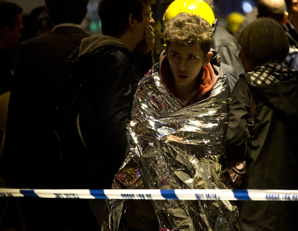 """A man wraps himself in an emergency foil blanket provided by rescue services following an incident at the Apollo Theatre, in London's Shaftesbury Avenue, Thursday evening, Dec. 19, 2013 during a performance , with police saying there were """"a number"""" of casualties. It wasn't immediately clear if the roof, ceiling or balcony had collapsed. The London Fire Brigade said the theatre was almost full, with around 700 people watching the performance. A spokesman added: """"It's thought between 20 and 40 people were injured."""""""