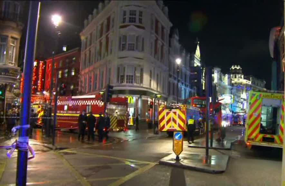"""This image taken from television shows emergency services attending an incident at the Apollo Theatre, illuminated at rear right, on London's Shaftesbury Avenue, Thursday evening, Dec. 19, 2013, during a performance at the height of the Christmas season, with police saying there were """"a number"""" of casualties. It wasn't immediately clear if the roof, ceiling or balcony collapsed during a performance."""