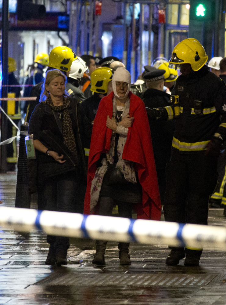 """A woman walks, bandaged and wearing a blanket given by emergency services, following an incident at the Apollo Theatre, in London's Shaftesbury Avenue, Thursday evening, Dec. 19, 2013, during a performance at the height of the Christmas season, with police saying there were """"a number"""" of casualties. It wasn't immediately clear if the roof, ceiling or balcony had collapsed during a performance. Police said they """"are aware of a number of casualties,"""" but had no further details."""