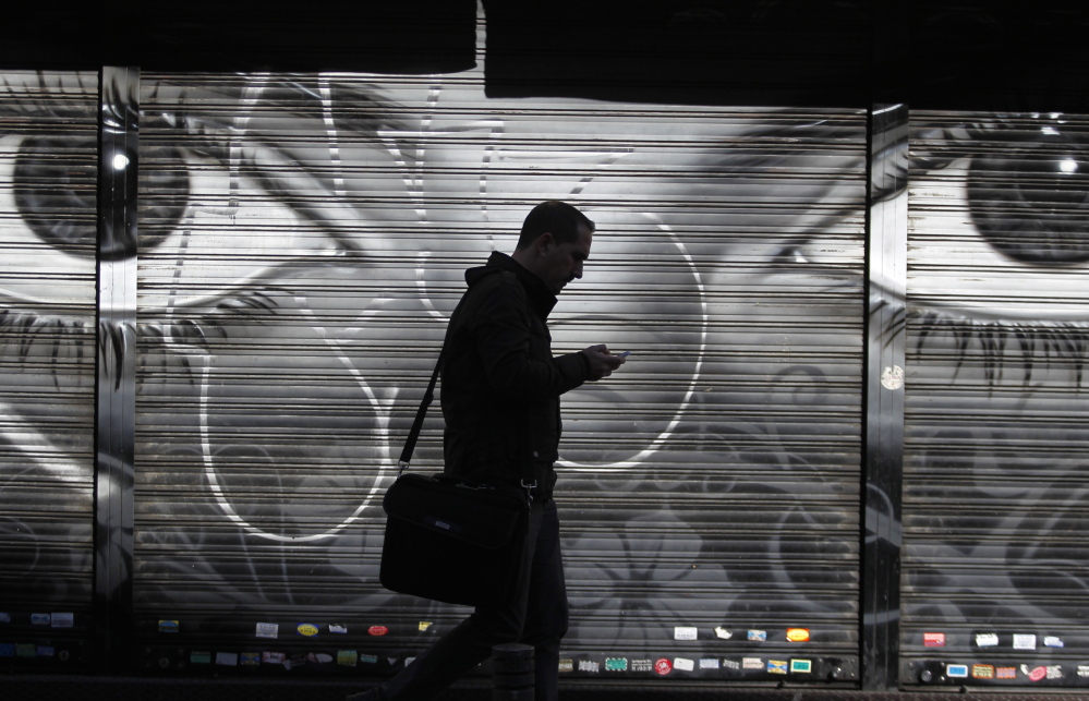 The watchful eyes of a poster follow a cellphone user in Madrid. The national debate over U.S. government surveillance efforts seems to be shifting in favor of reining in the National Security Agency' expansive spying powers.