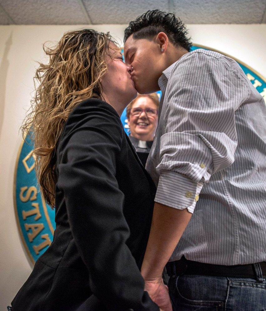 Desiree Padilla, left, and her partner Betty Garcia kiss after exchanging vows in a ceremony performed by the Rev. Judith Maynard, background, in Albuquerque, N.M., last summer. The New Mexico Supreme Court legalized same-sex marriage in the state Thursday, declaring in a ruling that it is unconstitutional to deny a marriage license to gay and lesbian couples.