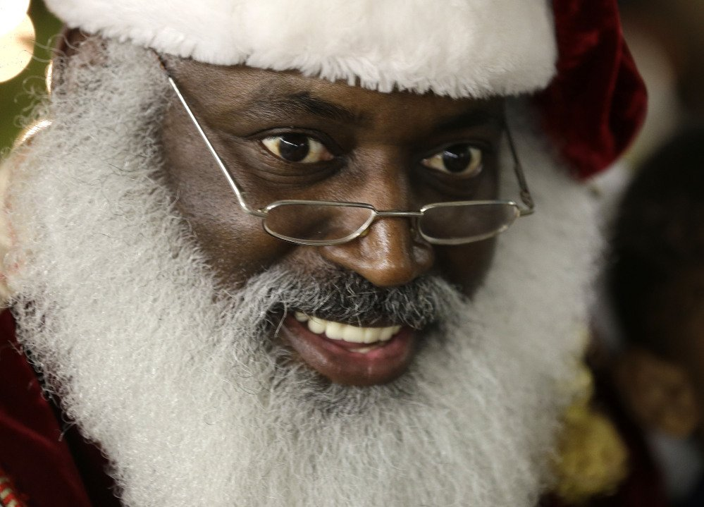 "Dee Sinclair, portraying Santa Claus, reads a story to children in Atlanta on Tuesday. ""Kids don't see color. They see a fat guy in a red suit giving toys,"" said Sinclair, 50, who bills himself as the ""Real Black Santa."""