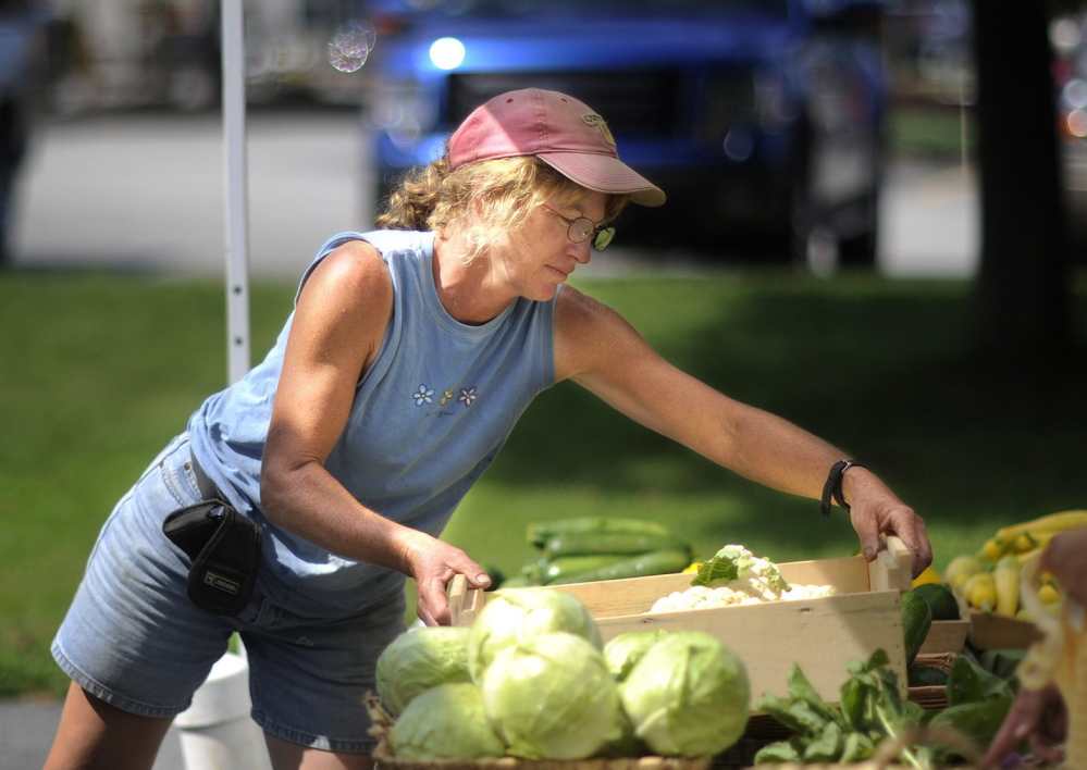 Cathy Karonis, who with husband Pete Karonis owns Fairwinds Farm in Topsham, works at the South Portland farmer's market in August. Pete Karonis said he welcomed a federal decision to back off stricter rules on produce safety.