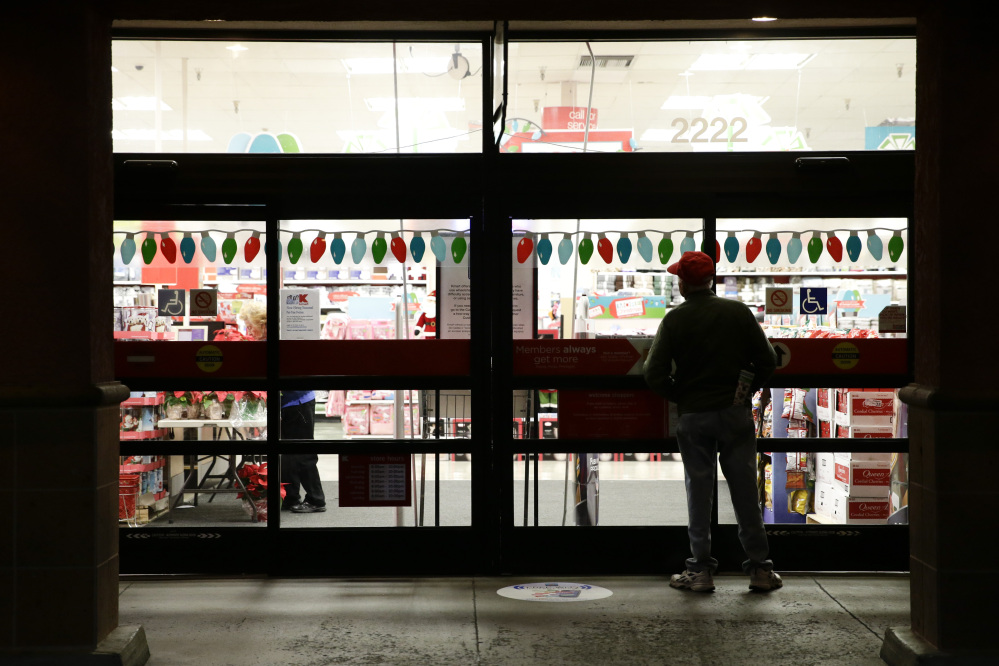 A shopper waits outside a Kmart store for it to open in Anaheim, Calif., on Thanksgiving night. Some retailers, disappointed by sales so far during the holiday shopping season, are staying open for several straight days, starting this weekend.