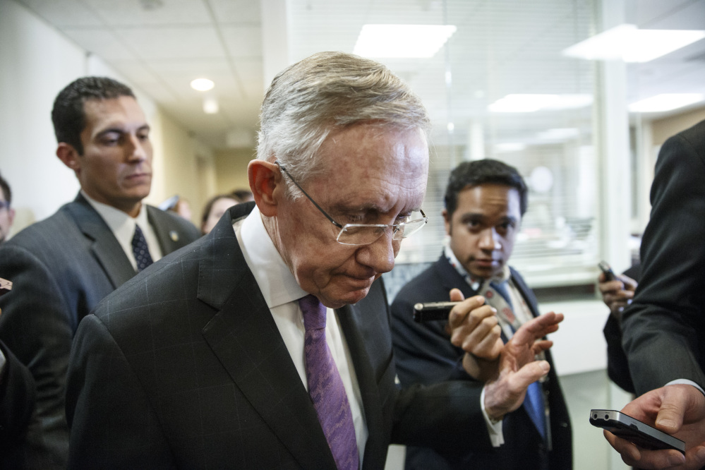 Senate Majority Leader Harry Reid is surrounded by reporters after talking about the final work of the Senate as the legislative year nears to a close, at the Capitol on Thursday.