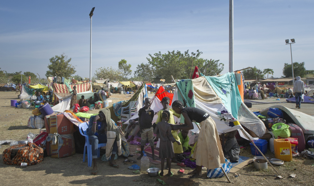 A displaced family sits with their belongings after seeking refuge at the compound of the United Nations Mission in South Sudan in Juba, South Sudan, on Thursday. South Sudan, the world's newest country, is threatened by rapidly escalating ethnic violence.