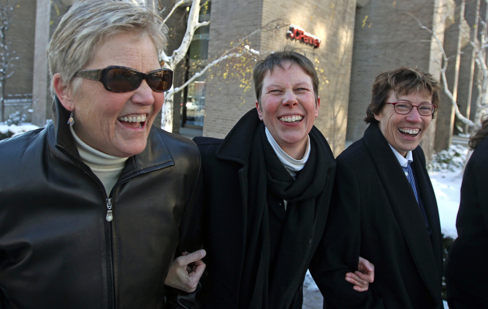 Laurie Wood, left, and her partner, Kody Partridge, center, walk with their attorney Peggy Tomsic after leaving the courthouse in Salt Lake City on Dec. 4. A federal judge struck down Utah's same-sex marriage ban Friday.